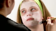 Close up hand of cosmetologist applying cream mask on face of teenage girl video