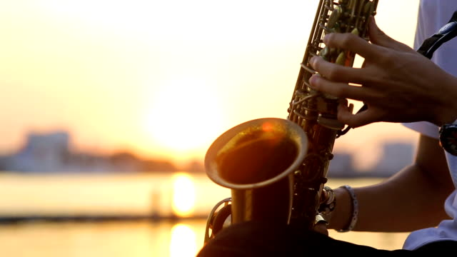 Close up hand of saxophone players with sunset video