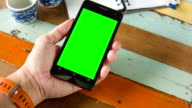 Close up hand using smart phone with blank green screen for chroma key video