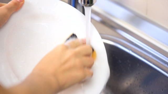 Close up hands of woman washing dishes in the kitchen video