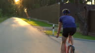 Close up hipster on bike in the city at sunset. Shot with sunflare and without face. video
