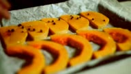 Close up man hands pour pepper pumpkin slices on baking sheet. Healthy food video