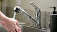 Close up man washing hands kitchen sink, slow motion, overcrank video