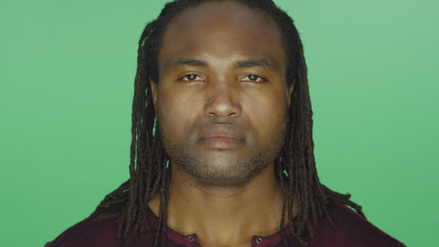 Close up of a black man with dreads looking serious, on a green screen studio background video