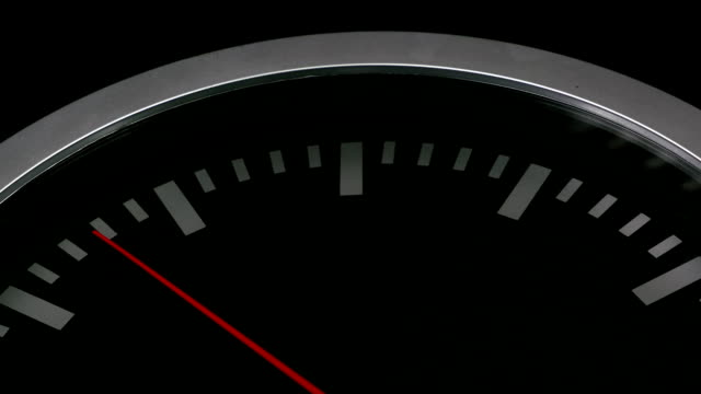 Close up of a black wall clock isolated on black background. Red second hand passing by video