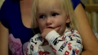 Close Up of a cute Little Girl sitting on her Mother hands at home video