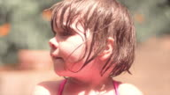 Close up of a cute little girl with wet hair playing outside and making silly faces video