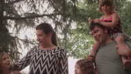 Close up of a family walking together under trees video