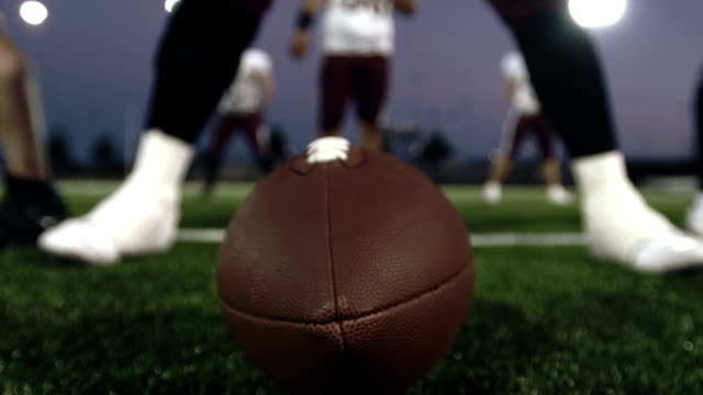 Close up of a football player's hand snapping the ball to the quarterback video