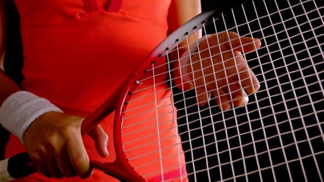 Close up of a girl tennis player's hand adjusting the net of her tennis racket, black background video
