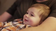 Close up of a little boy sitting on his father's lap and watching television video