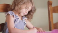 Close up of a little girl sitting at a table and coloring with crayons video