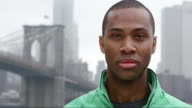 Close up of a man in running gear looking into the camera on an overcast day while standing in front of the brooklyn bridge video