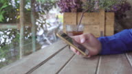 Close up of a man using mobile smart phone in coffee shop. video