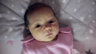Close up of a newborn girl with jaundice looking at the camera. video
