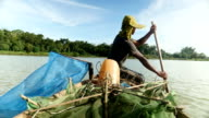 Shrimper fisherman paddles boat on a lake video