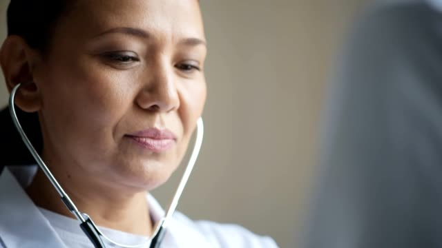 Close up of a professional female doctor using her stethoscope video