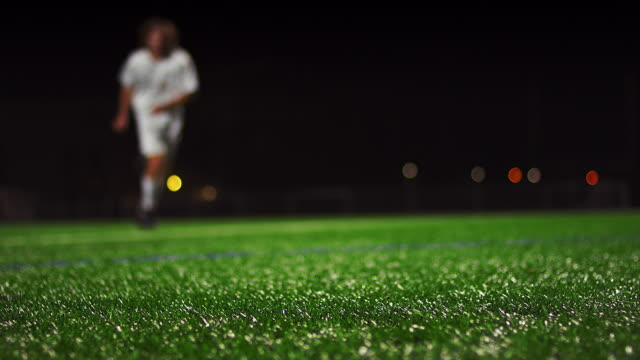 Close up of a soccer ball being kicked in slow motion at night video