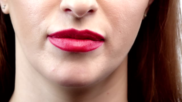 Close up of a woman lips with finger asking for silence, closeup video
