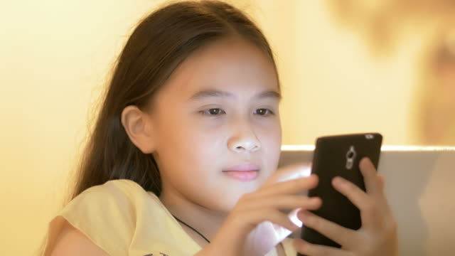 Close up of a young asian girl using smart phone video