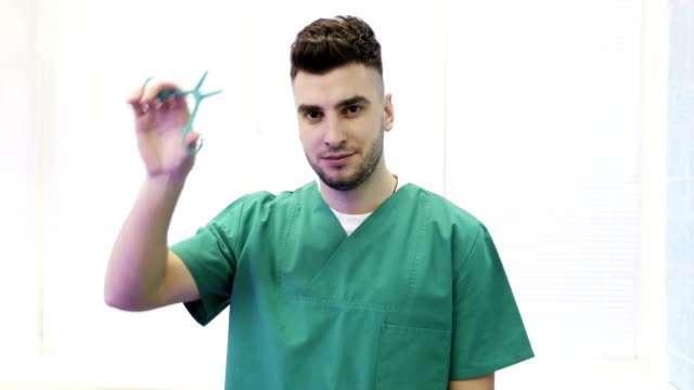 Close up of a young doctor in medical suit shows clips (scissors). video