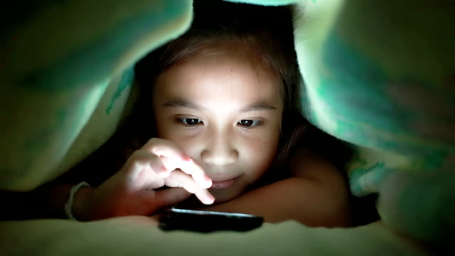 Close up of a young girl playing game under blanket video