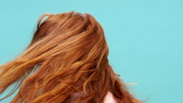 Close up of a young pretty girl with long red hair shaking her head isolated over blue background video