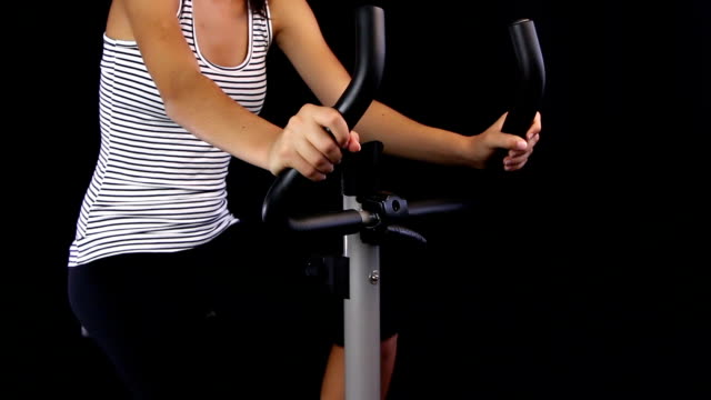 Close up of a young woman riding stationary bike video