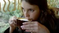 Close up of a young woman sipping her coffee in a cafe video