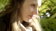 Close up of a young woman walking down the street on a sunny day in slow motion with lens flare video