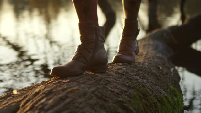 Close up of a young woman walking on a tree that has fallen into a pond video