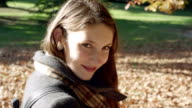 Close up of a young woman walking through the park and looking and smiling into the camera video