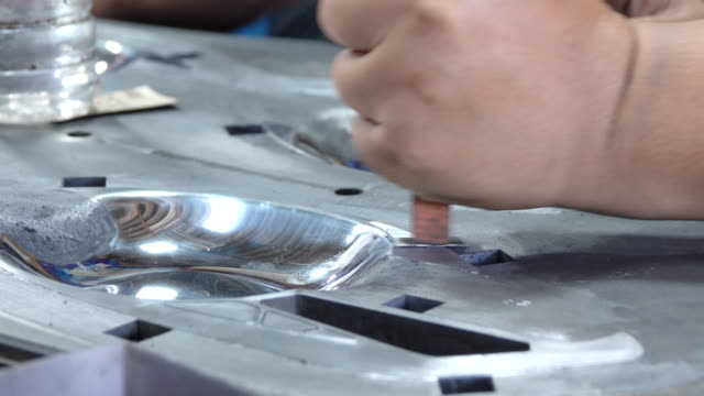 Close up of asian worker Polishing front metal mold. Dolly shot. video