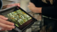 Close up of associate at marijuana shop pointing to product on a tablet video