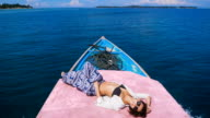 Close up of attractive model sunbathing on the deck of small yacht in the open sea. Young girl dressed in black swimsuit, blue trousers and black sunglasses is lying on rostrum of a ship and enjoying her cruise video
