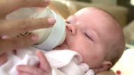 Close up of baby being fed milk from bottle in nursery video