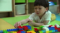 Close up of baby boy playing with colorful plastic bricks. video