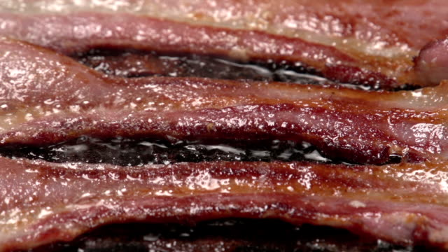 Close up of bacon frying video