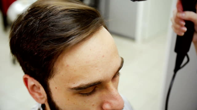 Close up of barber blow drying hair of the client after the haircut. Slow motion video