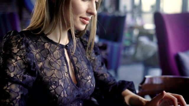 Close up of beautiful woman in black sexy decolette dress sitting in cafe and using modern laptop. Businesswoman working as a freelancer in mobile office at the table typing text on digital device video