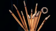 Close up of burning incense sticks with smoke over black background,rotating video