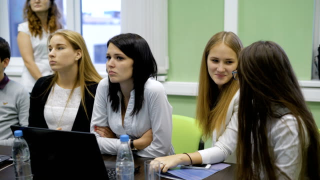 Close up of business team preparing the presentation of their project. Four young girls sitting at the desk, smiling and discussing their teamwork. Two girls are listening to speaking partner video