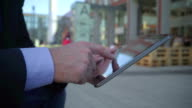 Close up of businessman's hand browsing tablet, steadicam video