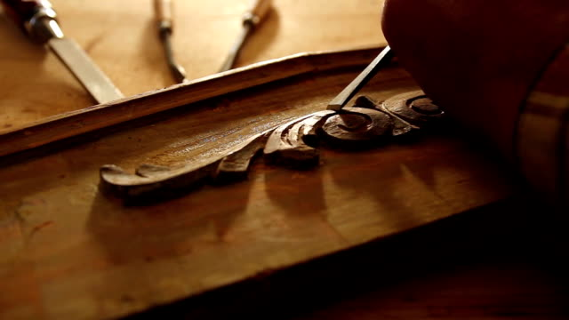 Close up of  carpenter restoring old furniture with chisel. video