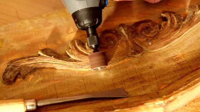 Close up of carpenter sanding wood with engraver tool. video