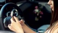 Close up of Caucasian female using smartphone in car. Blurred car interior background video