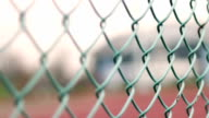 Close up of chain-link fence near a tennis court in country club or park video