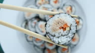 Close up of chopsticks holds sushi maki gunkan roll over a plate video