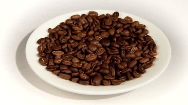 Close up of coffee beans. Loop rotation. Front of the camera rotates white plate with coffee beans video