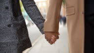 Close Up Of Couple Holding Hands Walking Along City Street video